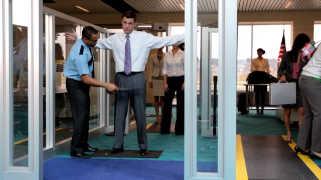 Travelers are screened at airport security checkpoint video