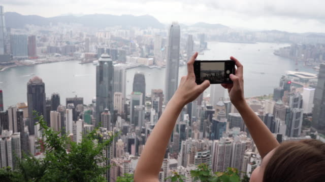 Travelers are using mobile phones to take pictures of Hong Kong city
