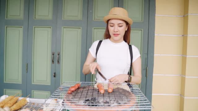 Travelers girls are fun to try grilled food on the stove manually.Asian woman Enjoying for landmark of Bangkok Wat Phra Kaeo in Bangkok City