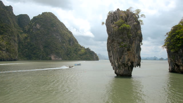 traveling boat pass trough Ko Tapu island in rainy day. video