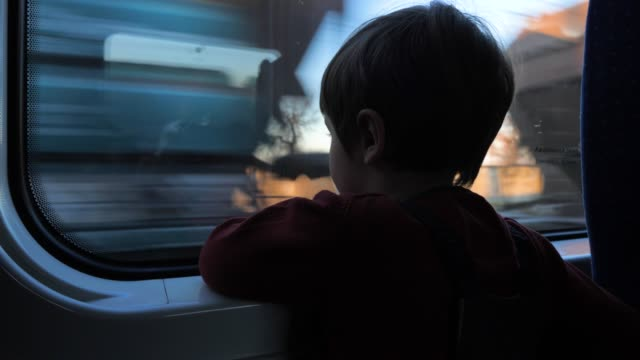 traveling by train. boy at train. cute 5 years old boy looking through the window in the train. traveling with children. child looking through the window. - passare davanti video stock e b–roll