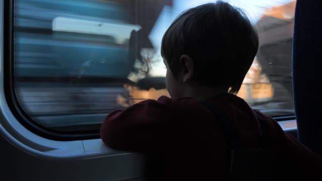 reisen mit der bahn. junge am zug. niedlicher 5-jähriger junge, der durch das fenster im zug schaut. reisen mit kindern. kind schaut durch das fenster. - vorbeigehen stock-videos und b-roll-filmmaterial