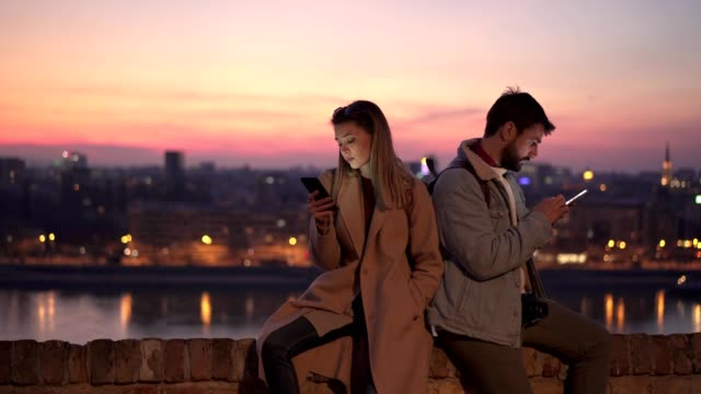 Traveling couple with relationship difficulties sitting on a for wall back to back Young traveling couple with relationship problems using mobile phones while sitting back to back on a city fort wall. back to back stock videos & royalty-free footage