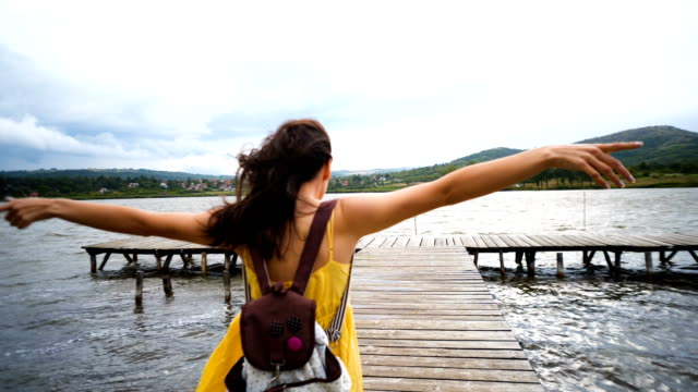 traveling girl on the wood pier. pretty young woman with backpack . - donna valigia solitudine video stock e b–roll