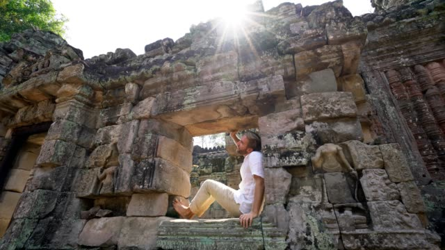 Traveling male tourist sitting on ancient temple window contemplating and enjoying the atmosphere of the Cambodian architecture