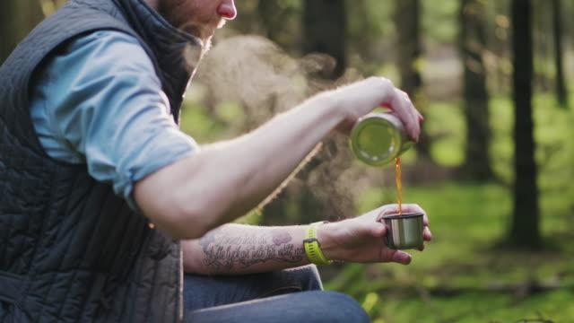 Traveling man vandring genom en tallskog sitter ner för att dricka lite kaffe video