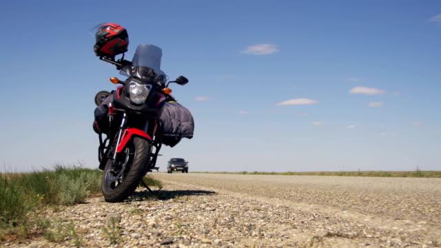 viaggiare su una moto. moto viaggi. stand motociclistici vicino alla strada e auto di passaggio - sussex occidentale video stock e b–roll