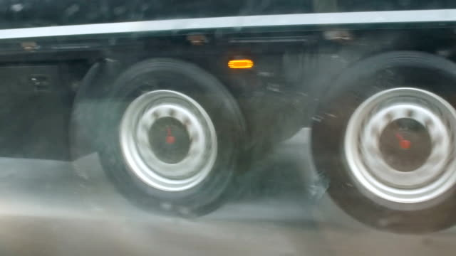 Traveling thought dangerous thunderstorm on the highway, wheels of truck video