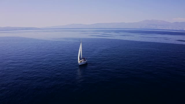 Traveling with a sailboat, sailing along the seas stock video Aerial drone point of view, sunny blue ocean, real time stock video... recreational boat stock videos & royalty-free footage