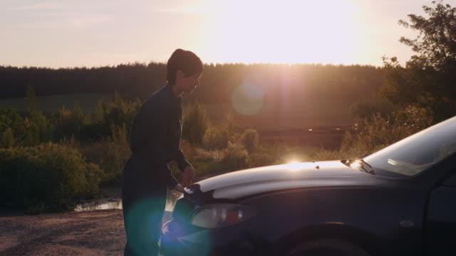 Traveller near broken car at sundown. video