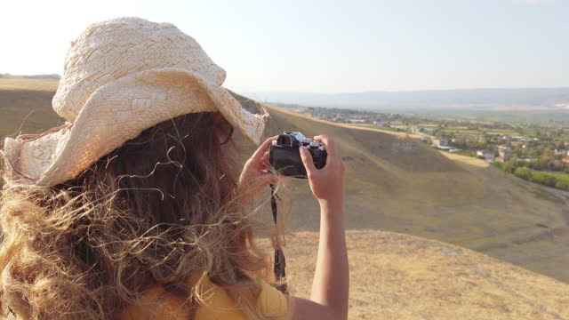 Traveller tourist photographer girl is shooting photos of Pamukkale Travertines  from ancient ruins of Laodicea on the Lycus