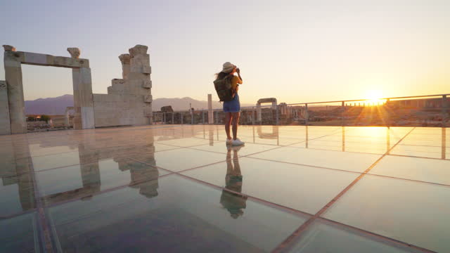 Traveller tourist photographer girl  is taking photos in ancient ruins of Laodicea on the Lycus at sunset, Pamukkale