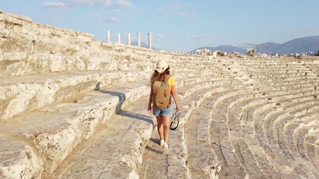 Traveller tourist photographer girl is walking behind the columns holding a camera in ancient ruins of amphitheatre in Laodicea on the Lycus at sunset, Pamukkale