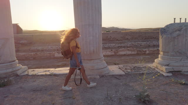 Traveller tourist photographer girl is walking behind the columns holding a camera in ancient ruins of Laodicea on the Lycus at sunset, Pamukkale