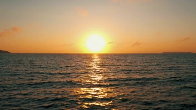 vídeos de stock e filmes b-roll de travelling above the ocean sunrise aerial view - linha do horizonte sobre água