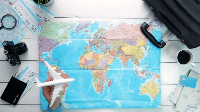 Travelling concept Top view traveler's hand flying a toy airplane above the world map at white wooden desk video