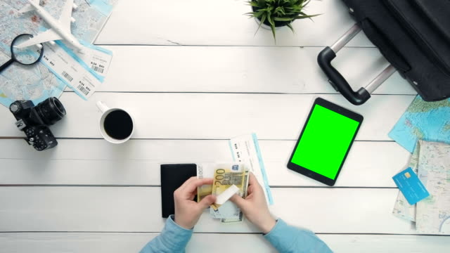 Travelling concept Top view traveler's hands checking money and ticket and digital tablet with green screen lying at white wooden desk video