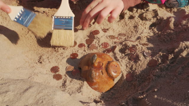 Treasure hunting. Kids playing archaeologists, unearthing the old piggy bank discovered hidden in the sand on a beach and picking coins.