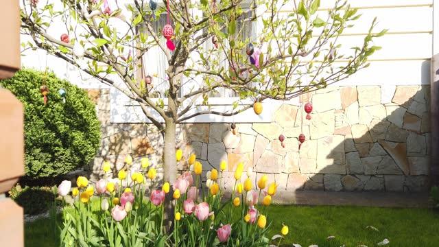 vídeos y material grabado en eventos de stock de arbol decorado con huevos de pascua y tulipanes en el jardín de primavera - ornamentado