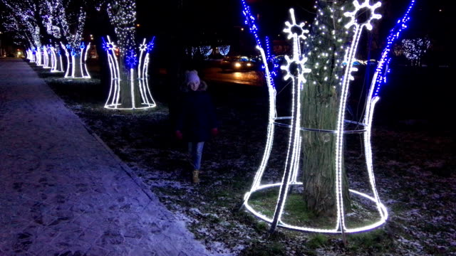 Trees with New Year's illumination and LED garlands of light bulbs. The street is decorated with New Year's lights. A child strolls in a winter park, in the evening. video
