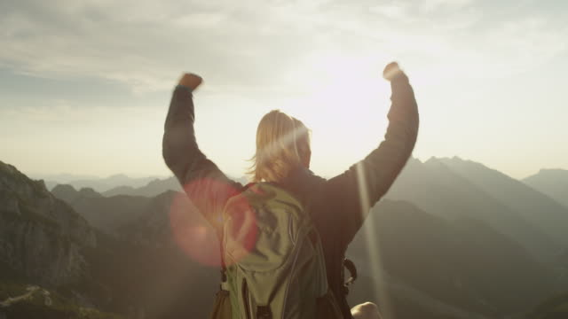 lens flare: trekker celebrates reaching mountaintop on a sunny summer day. - пик стоковые видео и кадры b-roll