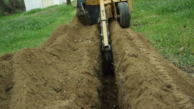 a trencher cuts a trench in the grassy ground outdoors near a storage warehouse - lama oggetto creato dall'uomo video stock e b–roll