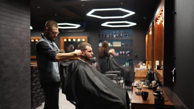 Trendy barber cuts bearded man's hair with a clipper in barbershop. Men's hairstyling and hair cutting in salon. Grooming the hair with trimmer. Hairdresser doing haircut in retro hair salon. Tracking