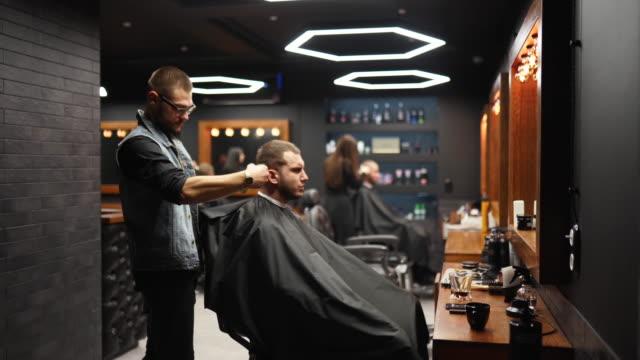 vidéos et rushes de le barbier à la mode coupe les cheveux d'homme barbu avec une tondeuse dans le salon de coiffure. coiffure et coiffure pour hommes dans le salon. grooming les cheveux avec coupe-coupe. coiffeur faisant la coupe de cheveux dans le salon de coiffure rétr - coiffeur