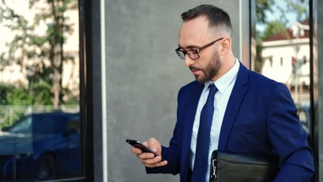 trendig affärsman i kostym och slips använder smartphone som går nära modern byggnad. 4k dragon red kamera - formella kontorskläder bildbanksvideor och videomaterial från bakom kulisserna