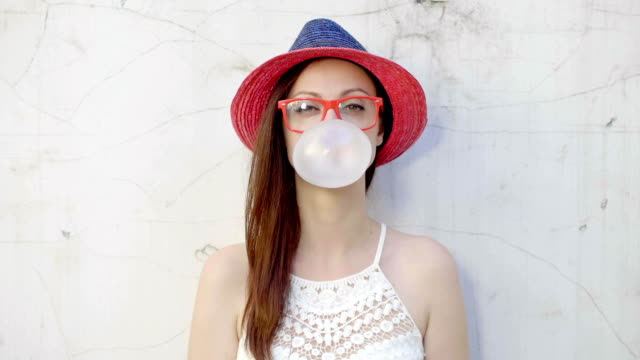 Trendy fashionable girl blows big bubble from bubble gum video