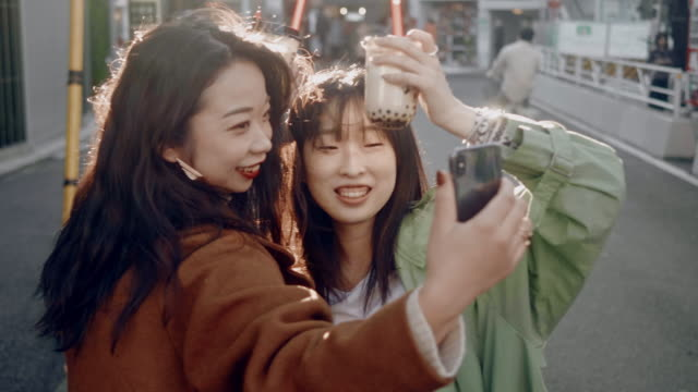 vídeos de stock e filmes b-roll de trendy japanese female friends taking selfies with bubble tea in the sunset - cultura jovem