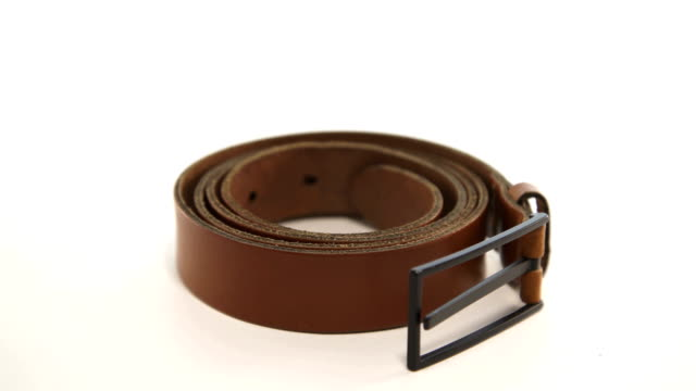 trendy leather belt with buckle rotate on white background - затягивание стоковые видео и кадры b-roll