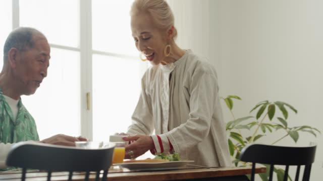 朝食時に夫にコーヒーを持って来るトレンディな先輩日本人女性 - 老夫婦点の映像素材/bロール