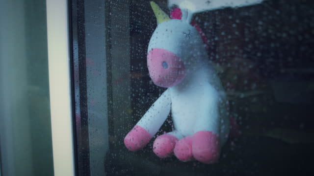4K unicórnio moderno brinquedo macio observando a chuva - vídeo