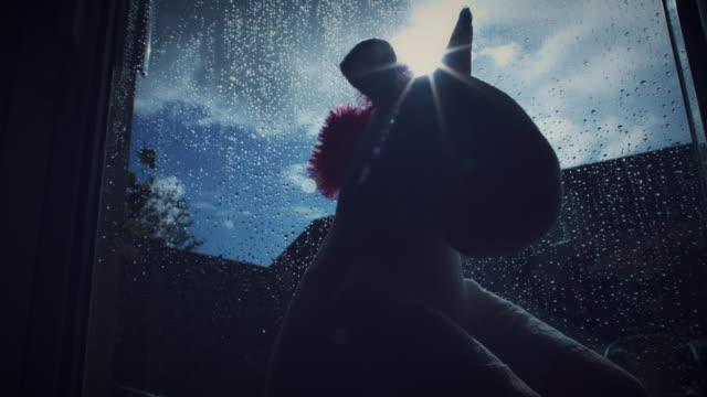4K moda unicornio peluche viendo la ventana - vídeo