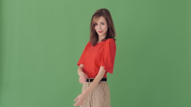 trendy woman with arms crossed over green background - comparsa video stock e b–roll