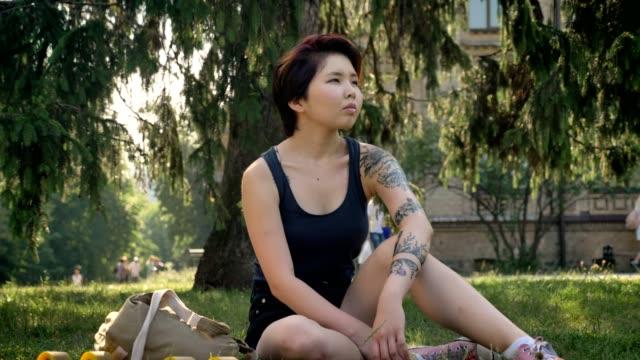 trendige jungen asiatischen weiblichen hipster mit tattoo sitzen auf dem rasen im park in der nähe von universität, nachdenklich - tätowierung stock-videos und b-roll-filmmaterial