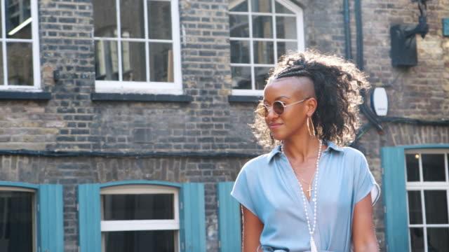 stockvideo's en b-roll-footage met trendy jonge vrouw in blauwe jurk zwart en ronde zonnebril lopen op de straat verleden camera, verlicht - street style