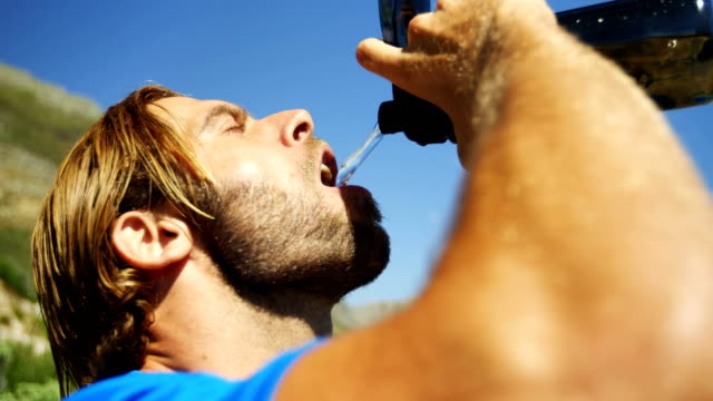 Triathlete man drinking water on a sunny day video