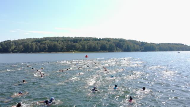 triathlon swimmers in lake - triatleta video stock e b–roll