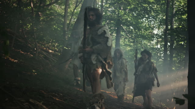 vídeos de stock e filmes b-roll de tribe of hunter-gatherers wearing animal skin holding stone tipped tools, explore prehistoric forest in a hunt for animal prey. neanderthal family hunting in the jungle or migrating for better land - evolução