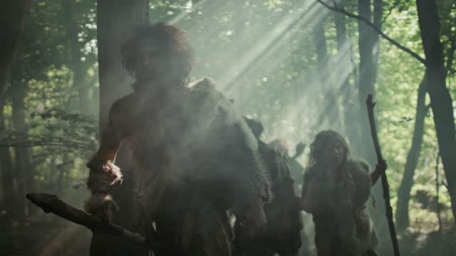 stam av jägare-samlare bär djurhud hålla sten tippas verktyg, utforska förhistoriska skogen i jakten på djur byten. neanderthalfamiljen jagar i djungeln eller migrerar för bättre mark - forntida bildbanksvideor och videomaterial från bakom kulisserna