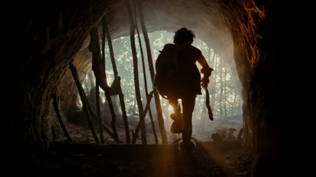 Tribe of Hunter-Gatherers Wearing Animal Skin Live in a Cave. Leader Holds Stone Tipped Tool, Leaving Cave going to Hunt for Animal Prey in the Prehistoric Forest, Female Cooks Food on Bonfire.