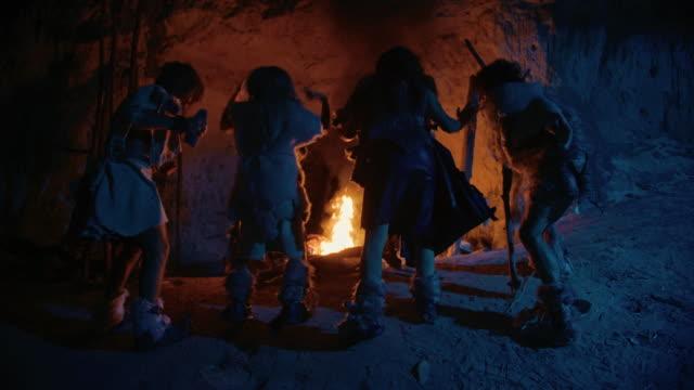 vídeos de stock, filmes e b-roll de tribo de caçadores-coletores pré-históricos vestindo peles de animais dança em torno de fogueira fora da caverna à noite. família de neanderthal/homo sapiens que faz a religião pagan que dança perto do fogo vista traseira slow motion - civilização milenar