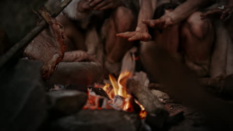 Tribe of Prehistoric Hunter-Gatherers Wearing Animal Skins Live in Cave at Night. Neanderthal or Homo Sapiens Family Trying to Get Warm at the Bonfire, Holding Hands over Fire, Cooking Food. Close-up Tribe of Prehistoric Hunter-Gatherers Wearing Animal Skins Live in Cave at Night. Neanderthal or Homo Sapiens Family Trying to Get Warm at the Bonfire, Holding Hands over Fire, Cooking Food. Close-up ancient stock videos & royalty-free footage