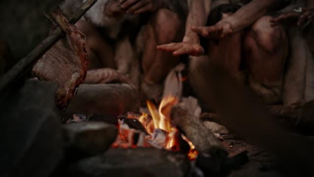 stam av förhistoriska jägare-samlare bär djurskinn lever i grottan på natten. neanderthal eller homo sapiens familj försöker bli varm vid brasan, hålla händerna över elden, matlagning mat. närbild - forntida bildbanksvideor och videomaterial från bakom kulisserna