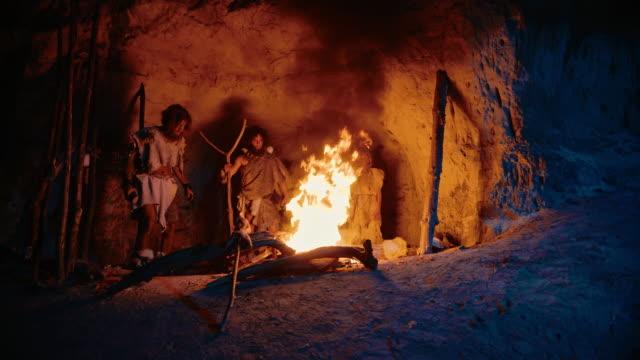 stam av förhistoriska jägare-samlare bär djurskinn stå runt brasan utanför grottan på natten. porträtt av neanderthal/homo sapiens familj gör pagan religion ritual nära fire - forntida bildbanksvideor och videomaterial från bakom kulisserna