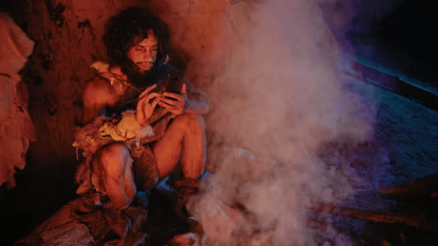 tribe of prehistoric, primitive hunter gatherer wearing animal skin uses smartphone in a cave at night. neanderthal / homo sapiens male browsing internet on mobile phone, watches videos - antica civiltà video stock e b–roll