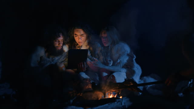tribe of prehistoric, primitive hunter-gatherers wearing animal skins use digital tablet computer in a cave at night. neanderthal or homo sapiens family browsing internet, watching videos, streaming - antica civiltà video stock e b–roll