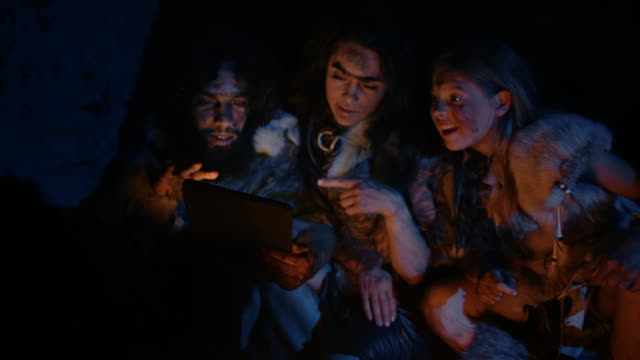tribe of prehistoric, primitive hunter-gatherers wearing animal skins use digital tablet computer in a cave at night. neanderthal or homo sapiens family browsing internet, watching videos, tv shows - antica civiltà video stock e b–roll